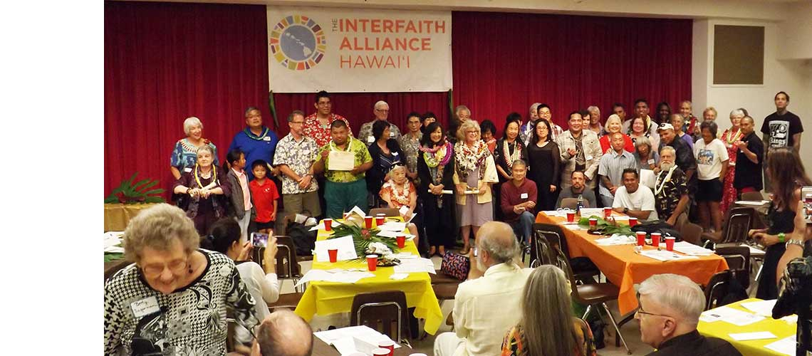 many smiling people grouped near the stage under The Interfaith Alliance Hawaii banner