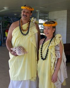 man with conch and woman with lei and flower head garland
