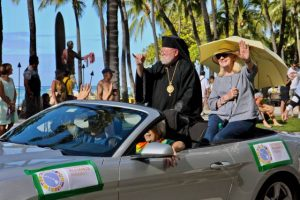 TIAH car with Bishop Sykes in black robes flashing a shaka at the Martin Luther King Jr. Parade 2017